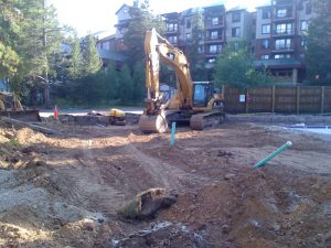 Large, yellow, excavator preparing to dig with apartment building in the background.