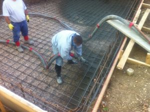 Man in rubber boots spraying gunite into steel frame with concrete pump hose.