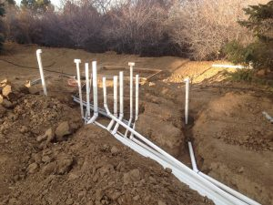 Complex system of white PVC pipes weaving through dirt trenches.